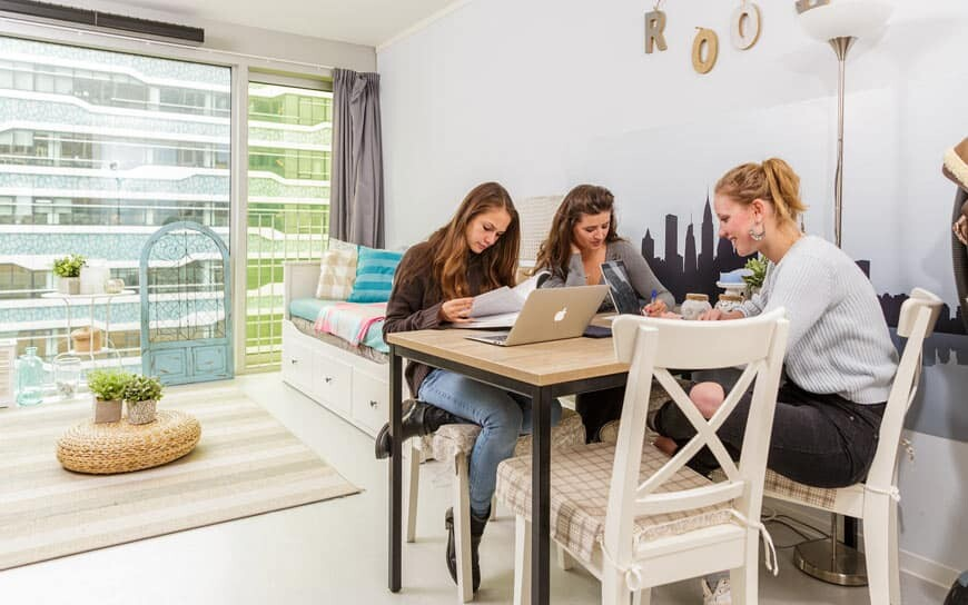 three students in a room with big windows