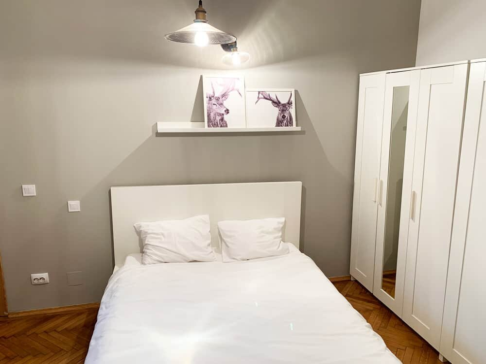 bedroom with grey wall and white pictures